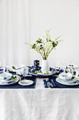 Blau-weiß gedeckter Tisch mit Frühlingsblumen