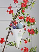 Handmade Easter decorations hung from branch of quince blossom