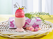Easter egg in egg cup and gift wrapped in handmade gift wrap
