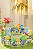 China eggs on DIY cake stand on Easter table decorated in blue and green