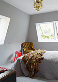 Double bed and armchairs in bedroom with grey, slightly sloping wall