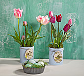 Tulips in tin cans painted pale blue decorated with tags with bird motifs