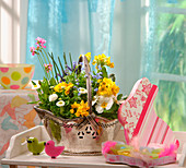 Rabbit-shaped, decoupage box and spring flowers in silver basket