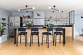Open-plan kitchen with counter and barstools