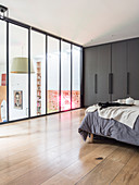 Double bed and grey fitted wardrobes in bedroom in glazed gallery