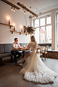 Bride and groom sitting at set table