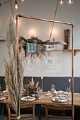 View of table set for wedding through copper wedding arch