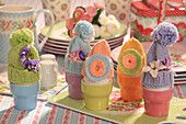 Knitted bobble-hat egg warmers on colourful Easter table