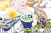 Chocolate eggs in crocheted basket on blue-and-white Easter table