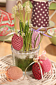 Easter eggs in crocheted covers in shade of red and pink around white grape hyacinth