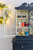 Christmas decorations and fairy lights in old kitchen dresser with open door