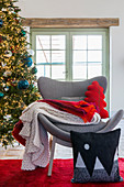 Cushions and blankets on grey modern easy chair in front of Christmas tree