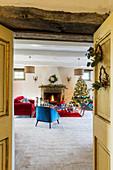 Weihnachtsbaum und Möbel in Blau und Rot vorm offenen Kamin