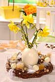 Wicker wreath decorated with feathers and eggs and narcissus in vase made from blown ostrich egg