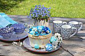 Marbled Easter eggs in basket and blue-and-white crockery on garden table