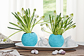 Osterdeko mit Traubenhyazinthen in blauen Vasen aus Pappmache