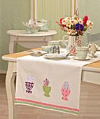 Tischläufer mit applizierten Eiern und Eierbechern auf dem Ostertisch