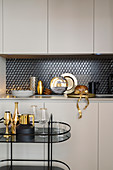 Serving trolley in front of fitted kitchen with glamorous golden accessories