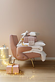 Geschenke, Decken und Kissen auf rosafarbenem Sessel