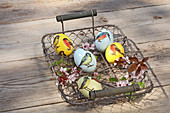 Easter eggs with bird motifs and flowering twigs in wire basket