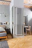 Radiator mounted on wall in studio apartment decorated in shades of grey