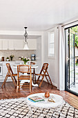 Folding chairs around pedestal table in front of kitchen counter in small interior