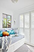 Tagesbett mit Bettkästen im hellen Raum mit Lamellentüren