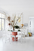 Large arrangement of branches on round table in white dining room