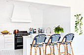 Rattan barstools with blue woven seats at kitchen counter