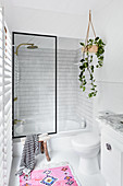 Tub-shower combo with glass screen and devil's ivy in small bathroom