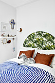 Bed with blue-and-white striped bed linen and exotic leaf pattern on headboard
