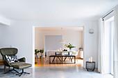 Ledersessel mit Fußschemel in hellem Wohnzimmer, Blick ins Esszimmer