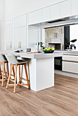 Fitted cupboards and counter in white, minimalist kitchen