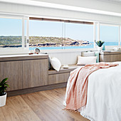 Sideboard with integrated window seat below horizontal panoramic window in bedroom