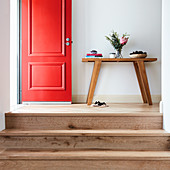Steps leading to console table in hallway and open red front door