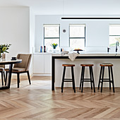 Barstools at counter and dining table in open-plan kitchen with parquet floor