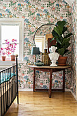 Fiddle leaf fig and bust on semicircular table against floral wallpaper