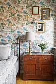 Old bedside cabinet in bedroom with floral wallpaper