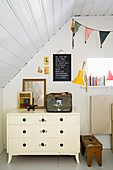 Old, white chest of drawers below sloping ceiling in child's bedroom