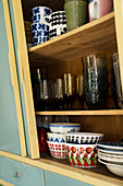 Old crockery and glasses in mid-century-modern kitchen cabinet