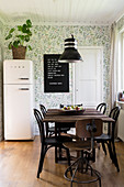 Black bistro chairs around table in dining room with floral wallpaper