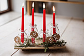 Handmade Advent arrangement of red candles in glass bottles