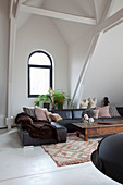 Black leather sofa and arched window in living room