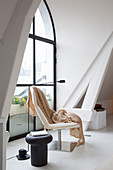 Blanket on modern easy chair and stool next to arched window