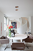 Upholstered chairs around oval dining table in front of spiral staircase
