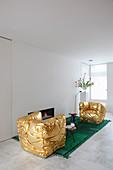 Goldene Sessel auf grünem Teppich vor eingebautem Kamin