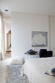 White bedroom with pale blue accents and black armchair