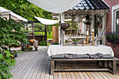 Dining table, bench and vintage-style accessories on large terrace