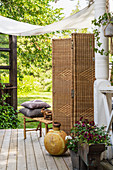 Wicker screen and vintage-style accessories on cosy terrace