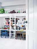 Desks below loft platform in children's bedroom decorated in white